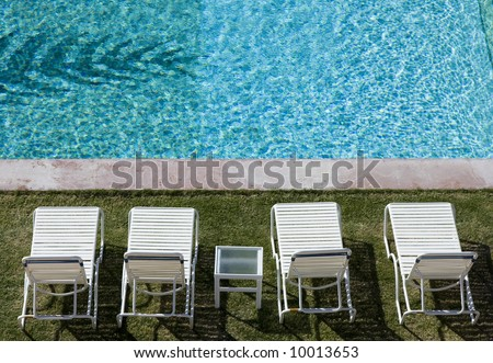 Ready for you -- a row of white lounge chairs by a resort pool.