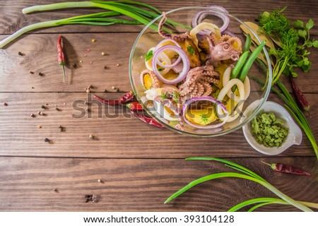 Ready fresh squid rings and tentacles of an octopus with stewed potatoes and greens in  rustic. top view - stock photo