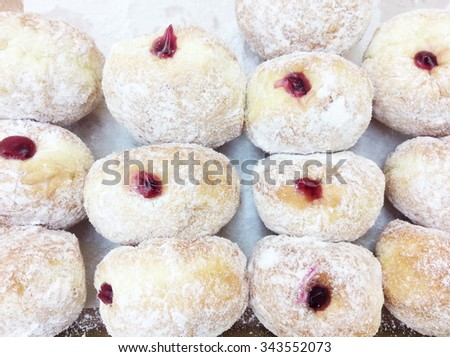 Ready-made donuts covered with powdered sugar on a tray