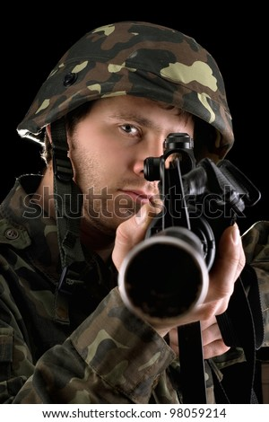 Ready soldier aiming a rifle in studio. Closeup
