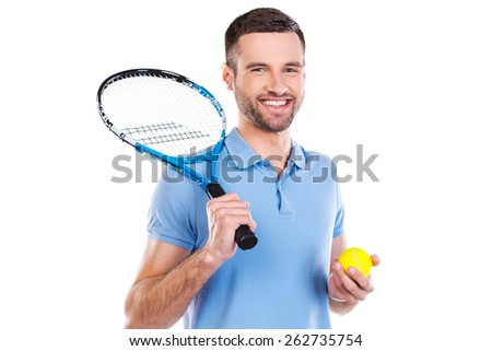 Ready to a big game. Confident young man holding tennis racket and smiling while standing against white background  - stock photo