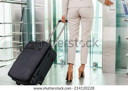 Ready to business trip. Rear view of businesswoman in formalwear pushing button while standing near elevator entrance