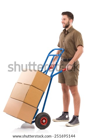 Ready to delivery. Happy delivery man waiting with a push cart and looking away. Full length studio shot isolated on white. - stock photo