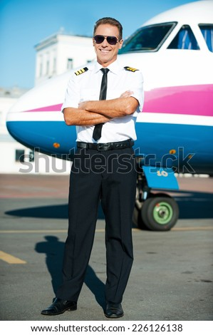 Ready to flight. Full length of confident male pilot in uniform keeping arms crossed and smiling with airplane in the background  - stock photo