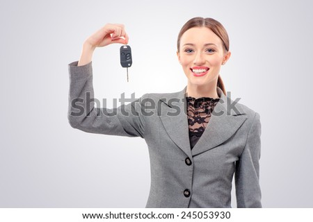 Ready to get on the road. Attractive young caucasian Woman with a car keys isolated on studio background. - stock photo