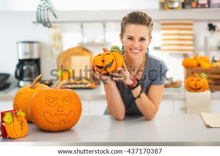Ready to halloween invasion. Smiling young woman showing ceramic pumpkin in halloween decorated kitchen.