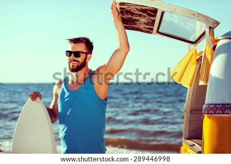 Ready to have some fun. Smiling young man holding skimboard and while opening a trunk door of his retro minivan with sea in the background  - stock photo