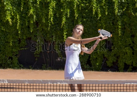 Ready to hit back. Young female tennis athlete swinging racket to hit coming ball white dress with miniskirt outdoor play court dark green fence background orange clay ground - stock photo