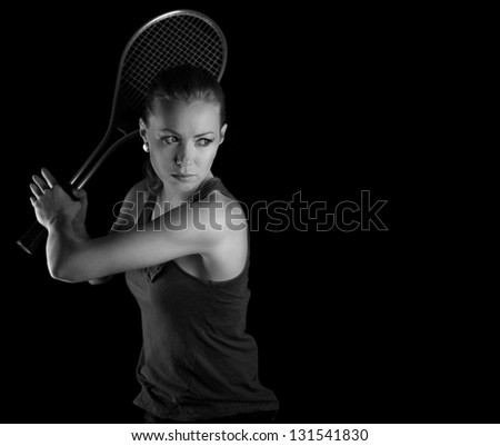 Ready to hit! Female tennis player with racket ready to hit a tennis ball. On black. - stock photo