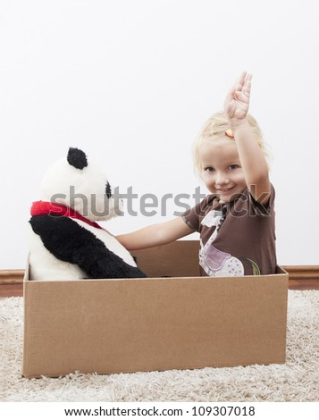 ready to move- little girl in a box with her teddy bear - stock photo