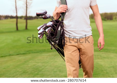 Ready to play. Close up of walking young golf player with special equipment on his shoulder. - stock photo