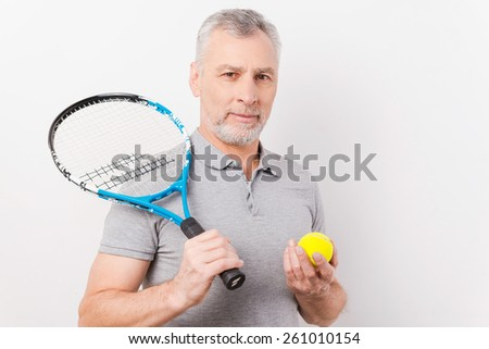 Ready to play. Confident grey hair senior man holding tennis racket and ball while standing against white background