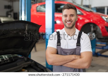 Ready to Repair Your Car. Smiling man in workshop posing with arms crossed. Waist up shot in auto repair shop. - stock photo