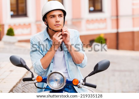Ready to ride. Handsome young man wearing helmet while sitting on scooter  - stock photo