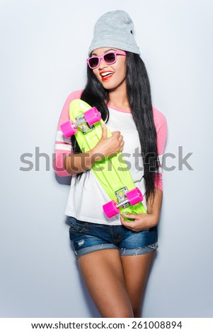 Ready to ride. Happy young African woman in funky clothes holding colorful skateboard and smiling while standing against grey background - stock photo