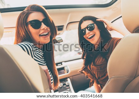 Ready to road trip! Rear view of two beautiful young cheerful women looking at camera with smile while sitting in car  - stock photo