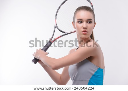 Ready to serve. Beautiful young woman in sports clothes holding tennis racket and looking away while standing against white background - stock photo