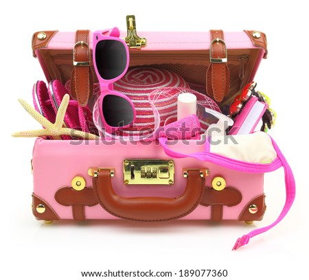 Ready to travel pink suitcase with summer equipment isolated  - stock photo