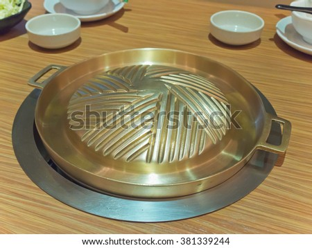 Ready-to-use brass grilling pan for Korean style BBQ - stock photo
