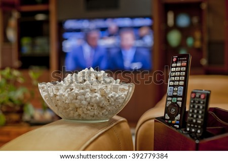 Ready to watch the game on TV with bowl of pop corn and remote - stock photo