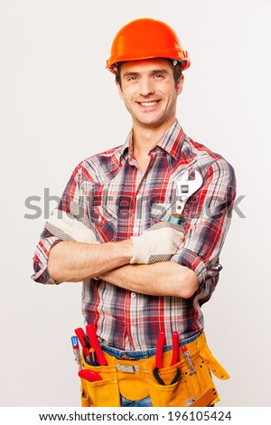 Ready to work. Handsome young handyman with tool belt holding wrench and smiling while standing against grey background - stock photo
