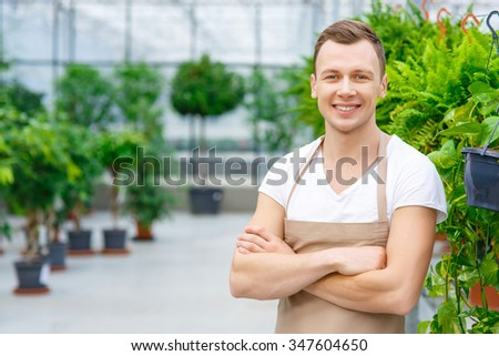 Ready to work. Young cheery greenhouse worker with folded hands standing in the greenhouse.