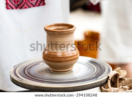 Ready wet clay pot on a pottery wheel in outdoor workshop - stock photo