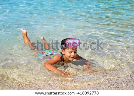 Real adorable toddler girl enjoying her summer vacation at beach
