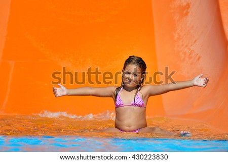 Real adorable toddler girl enjoying her summer vacation on waterslide at aquapark
