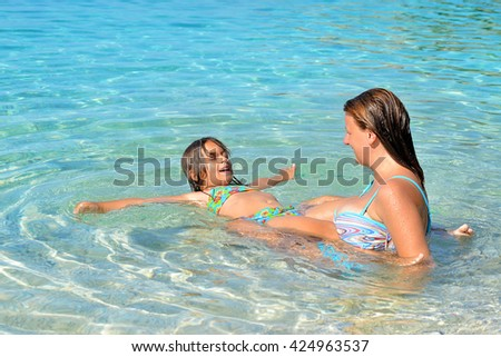 Real adorable toddler girl enjoying her summer vacation with her mother