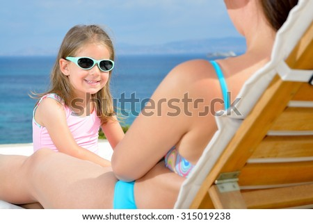 Real adorable toddler girl relaxing on the sunbed - stock photo