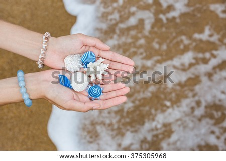 Real and vibrant plastic shells in girl's hands on the beach - stock photo