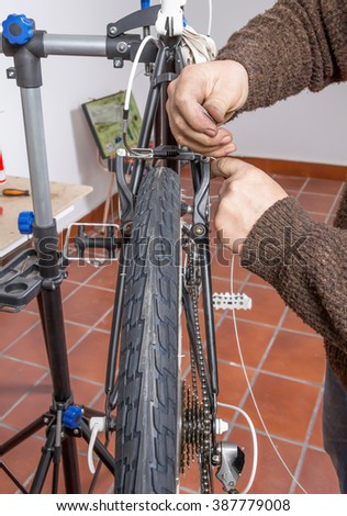 Real bicycle mechanic repairing black custom fixie bike in the workshop - stock photo