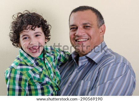 Real birthday celebration:  Young boy with brown hair in green plaid shirt and two missing front teeth posing with adult man with pepper hair and striped shirt smiling at the camera.  - stock photo