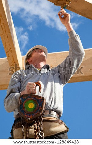 real builder at work with wooden  roof construction - stock photo