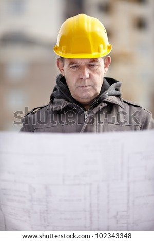 real builder with blueprints on construction site, natural light, focus on face - stock photo