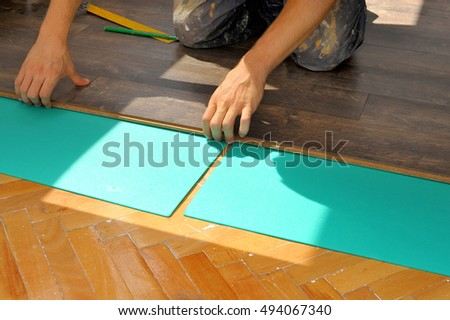 Real carpenter doing laminate floor work, renovation concept