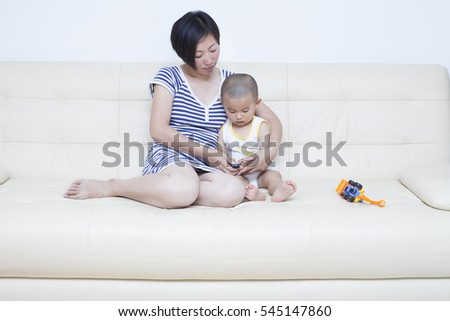 Real Chinese mother and son playing in sofa, Beijing, China