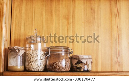 real comfort wooden kitchen with breakfast ingredients close up in glass, honey, oatmeal, milk, muesli