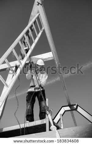 Real construction worker at work with winch on roof construction.Monochrome - stock photo