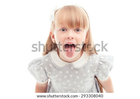 Real emotions. Nice smiling little girl opening her mouth and showing the tongue while standing isolated on white background.