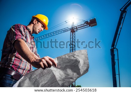 Real Engineer looking at his blueprint plan on construction site, crane and concrete pump seen in the background - stock photo