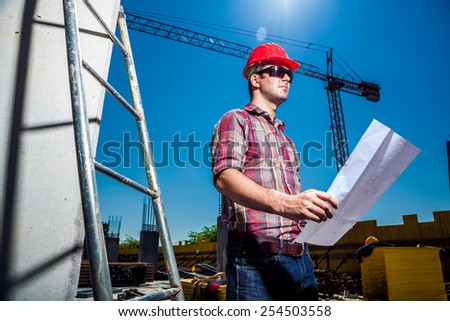 Real Engineer looking at his blueprint plan on construction site, ladder and crane seen in the background