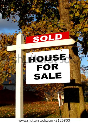 Real estate advertising sold rider insert over home owner house for sale sign on a wood post in a residential neighborhood street - stock photo