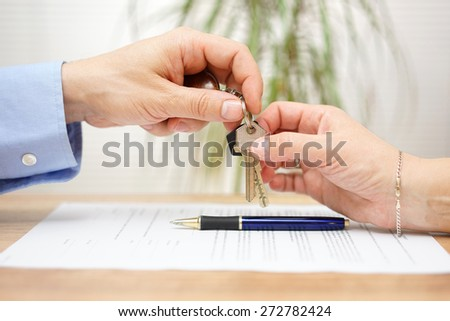 real estate agent gives house keys to his client after signing contract - stock photo