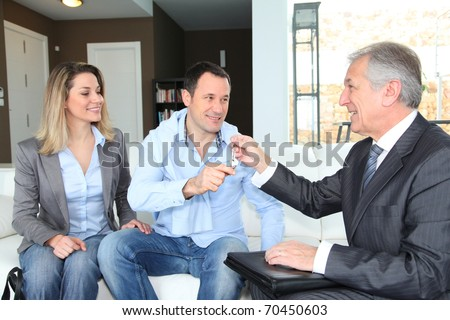 Real-estate agent giving house keys to young owners - stock photo