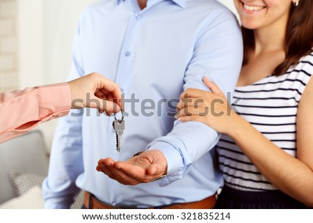 Real estate agent giving keys to young couple - stock photo