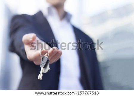 Real estate agent giving keys with buildings background - stock photo