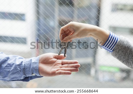 Real estate agent handing over a key to a customer - stock photo