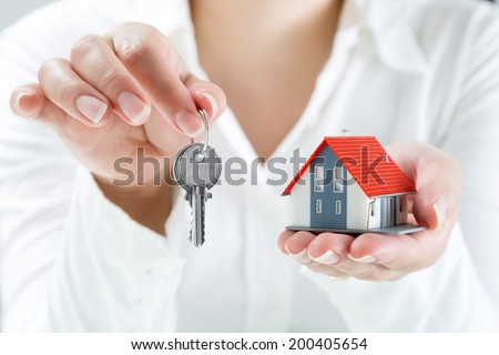 real estate agent handing over keys to home  - stock photo